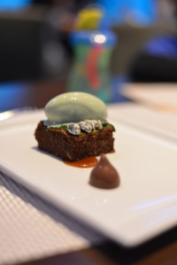 Dessert of pistachio ice cream and brownie and caramel.